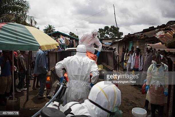 An ambulance team loads the body of a woman suspected of being infected with Ebola onto a truck for eventual cremation on October 14 2014 in Monrovia...