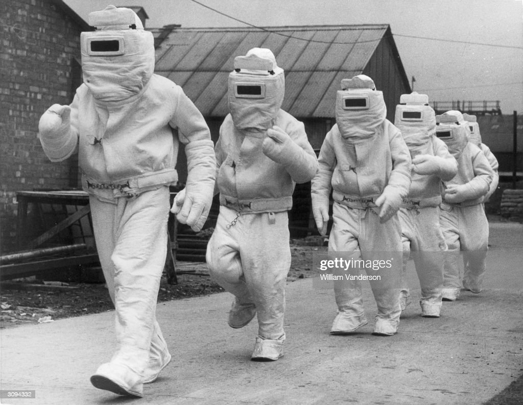 A demonstration of asbestos fire fighting suits designed for the Fleet Air Arm for rescuing airmen trapped in blazing aircraft