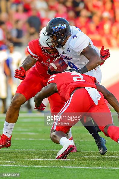 Tulsa Golden Hurricane running back D'Angelo Brewer is tackled by Houston Cougars linebacker Emeke Egbule and Houston Cougars safety Khalil Williams...