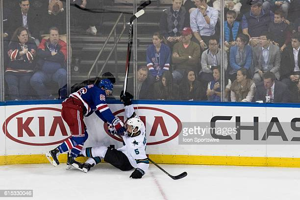 New York Rangers Center Josh Jooris sends San Jose Sharks Defenseman David Schlemko to the ice during the second period of a NHL game between the San...
