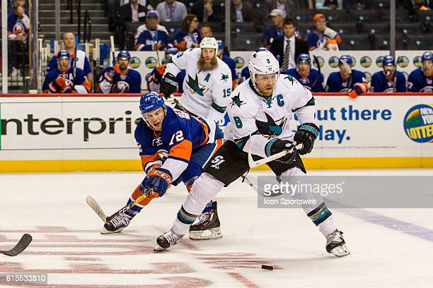 New York Islanders Left Wing Anthony Beauvillier reaches around San Jose Sharks Center Joe Pavelski during the first period of a NHL game between the...