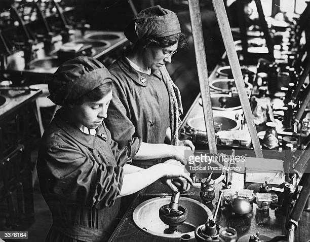 Two women war workers smoothing and polishing lenses