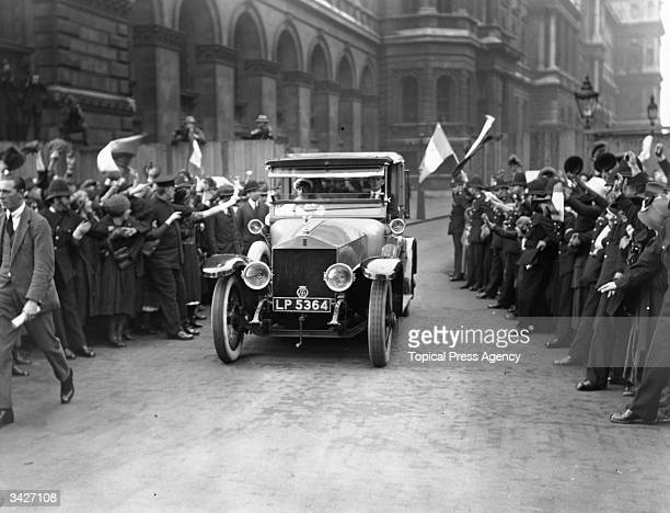 Police hold back crowds cheering delegates in their car outside the gates at Downing Street London during treaty negotiations between representatives...