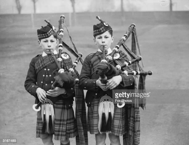Two young pipers serenade the arrival of the Christmas pudding at the Dr Barnardo's children's home at Kingston Hill