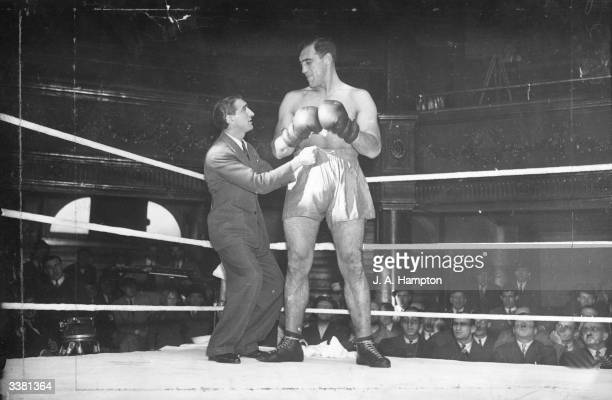 Italian heavyweight boxer Primo Carnera at the Ring in Blackfriars London having his shorts adjusted by Benny Huntman