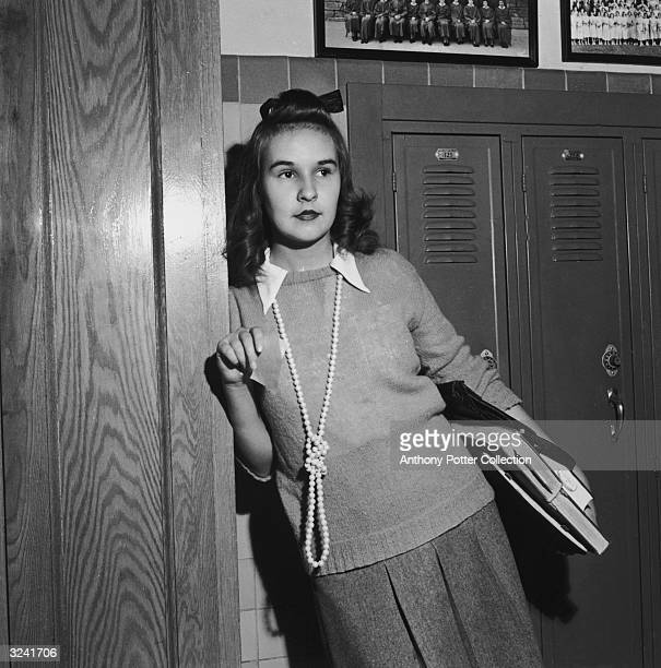 A teenaged girl leans next to a locker in a sweater a pleated skirt and long knotted beaded necklace Woodrow Wilson high school Washington DC