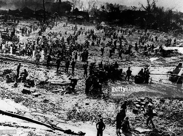 Half starved Philippino civilians mingle with their American saviours on the beach at Leyte Island following the routing of the Japanese forces