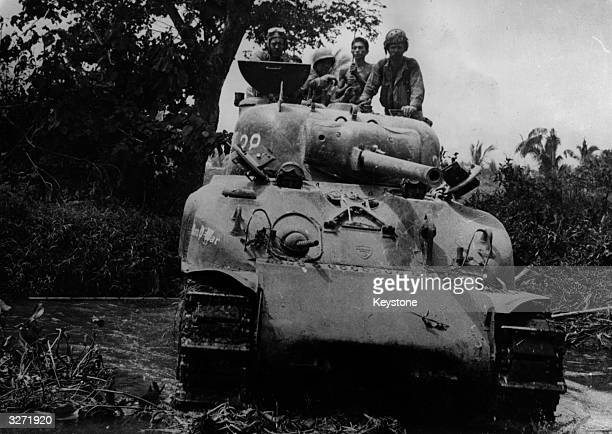 On Leyte Island members of the crew of a tank take a breather from the confines of its interior and scan the horizon for Japanese patrols to rout...