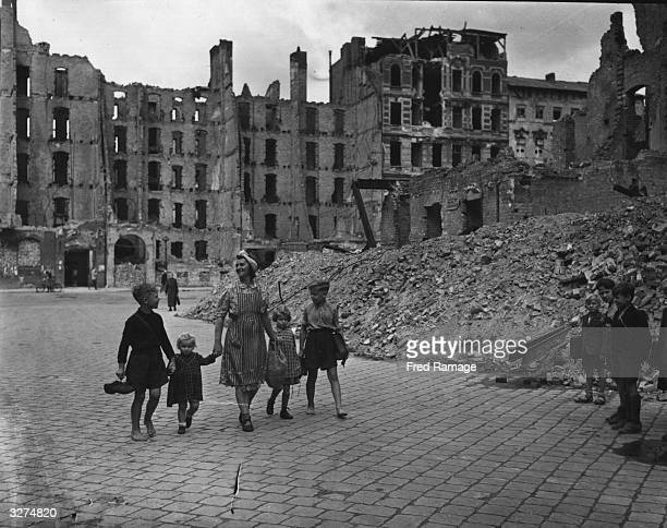 Elsa Gabriele passes by the battle ruins of Berlin as she accompanies her family to schoolThe boys carry their shoes to save on wear and tear
