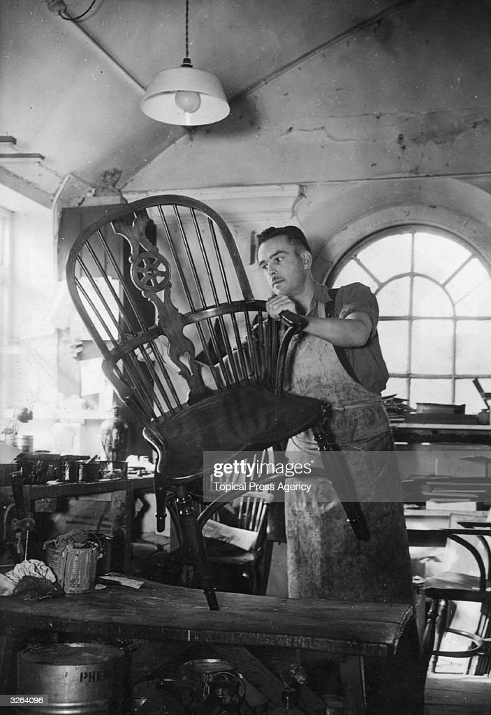 A man French at Messrs Nicholls James High Wycombe Buckinghamshire polishes a Windsor armchair for export to the USA