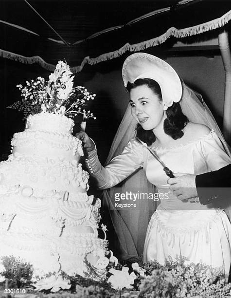 New bride Jane Withers licks her lips as she prepares to cut into her wedding cake at a reception for 600 people