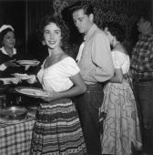 EXCLUSIVE Britishborn actor Elizabeth Taylor smiles as she holds a plate in a buffet line next to her first husband hotel heir Conrad 'Nicky' Hilton...