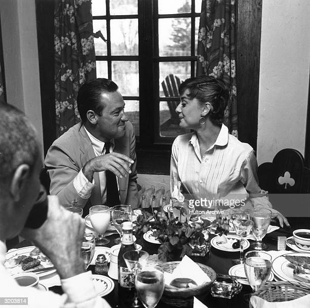 American actor William Holden and Belgianborn actor Audrey Hepburn smile while facing each other during a meal on the set of director Billy Wilder's...