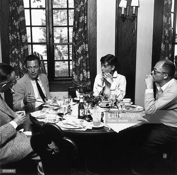 American actor William Holden speaks to Belgianborn actor Audrey Hepburn and Austrianborn director Billy Wilder during a meal on the set of Wilder's...