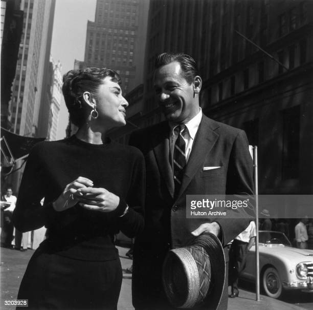 Belgianborn actor Audrey Hepburn and American actor William Holden laugh while facing each other on the set of director Billy Wilder's film 'Sabrina'...