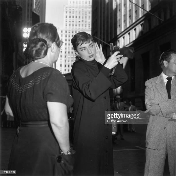 Belgianborn actor Audrey Hepburn fixes her hair while looking into a handheld mirror in front of skyscrapers on the set of director Billy Wilder's...