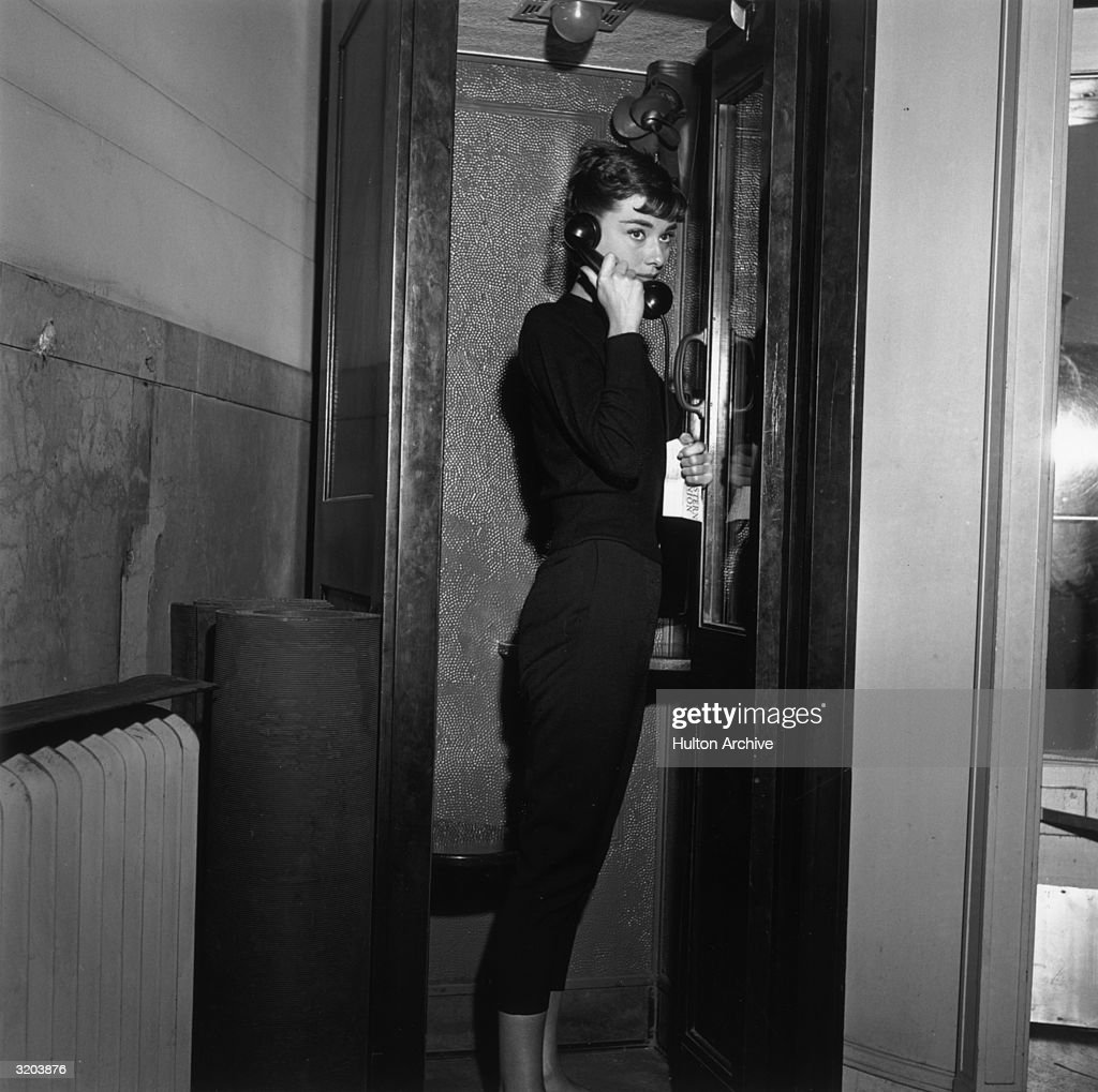 Belgian-born actor Audrey Hepburn (1929-1993), holding a Western Union telegram, stands in a telephone cabin with a receiver to her ear on the set of director Billy Wilder's film, 'Sabrina', New York City. Hepburn wears a dark sweater and Capri pants.