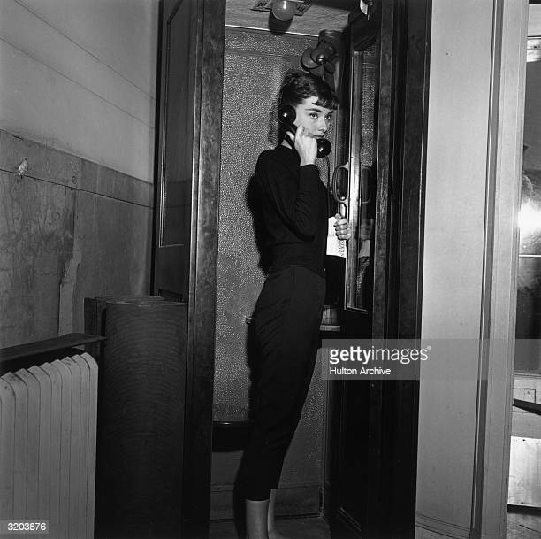 Belgianborn actor Audrey Hepburn holding a Western Union telegram stands in a telephone cabin with a receiver to her ear on the set of director Billy...