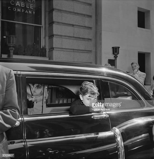 Belgianborn actor Audrey Hepburn leans out of a car window on the set of director Billy Wilder's film 'Sabrina' New York City Hepburn wears a dark...