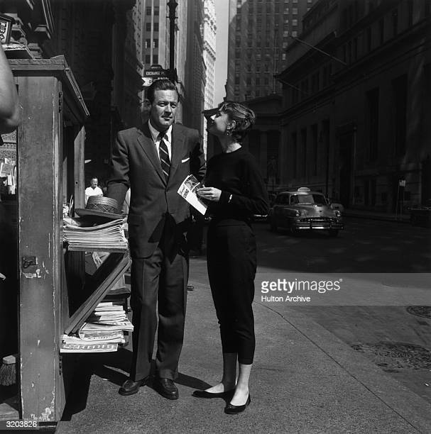 Fulllength image of American actor William Holden and Belgianborn actor Audrey Hepburn standing in front of a newspaper kiosk on the set of director...
