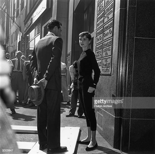 Fulllength image of American actor William Holden and Belgianborn actor Audrey Hepburn talking while standing in front of an office building on the...
