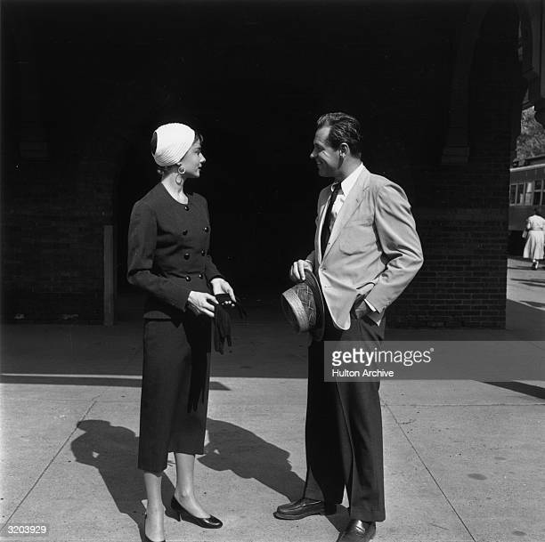 Fulllength image of Belgianborn actor Audrey Hepburn and American actor William Holden talking while standing in front of a train station on the set...