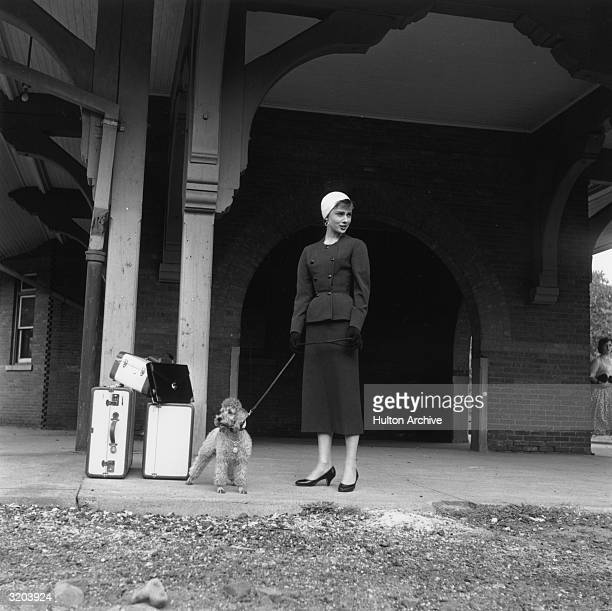 Fulllength image of Belgianborn actor Audrey Hepburn waiting in front of a train station with a toy poodle and luggage on the set of director Billy...