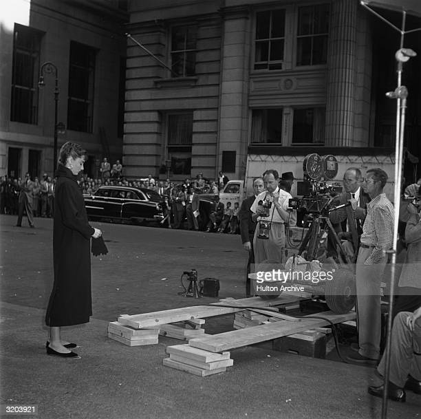 Fulllength image of Belgianborn actor Audrey Hepburn putting on gloves while standing on a sidewalk in front of a camera crew prior to shooting on...