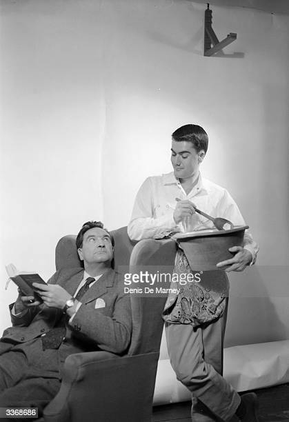 A scene from 'Tittertrotter' with a man stirring a large pudding bowl as he talks to another in an armchair Cast includes Winifred Shotter John...