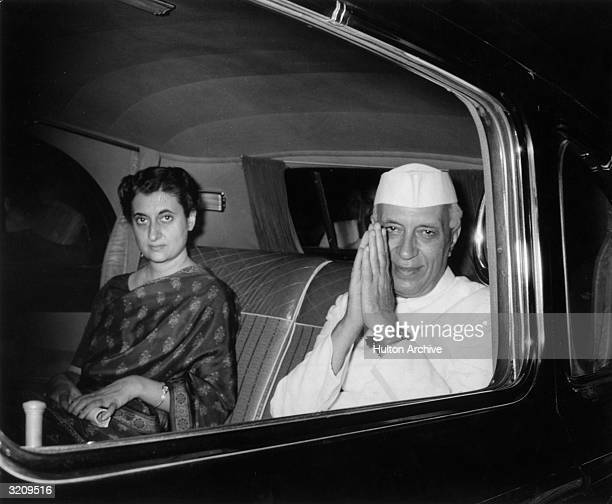 Indian prime minister Pandit Nehru clasping his hands in salute while sitting with his daughter Indira Gandhi in the backseat of a car