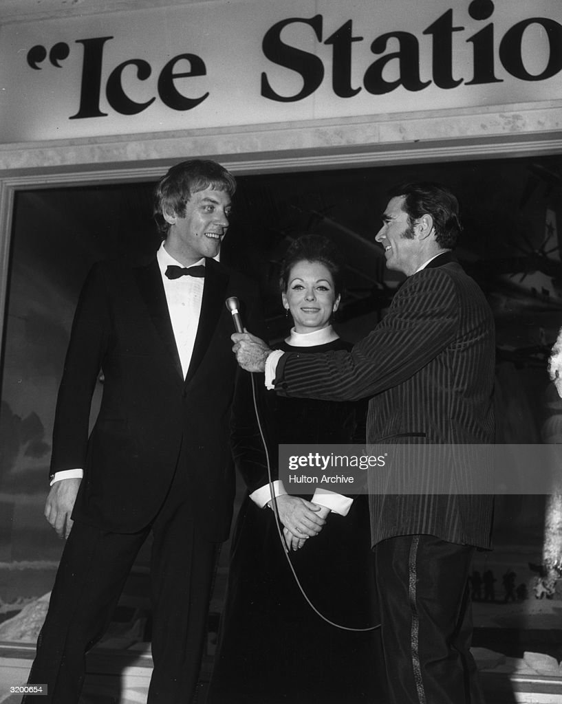 A low-angle view of Canadian actor Donald Sutherland (L), wearing a tuxedo, standing next to his first wife, actor Shirley Douglas, as he talks to columnist Army Archerd, at the premiere of director John Sturges's film, 'Ice Station Zebra,' Pacific's Cinerama Dome Theatre, Hollywood, California.