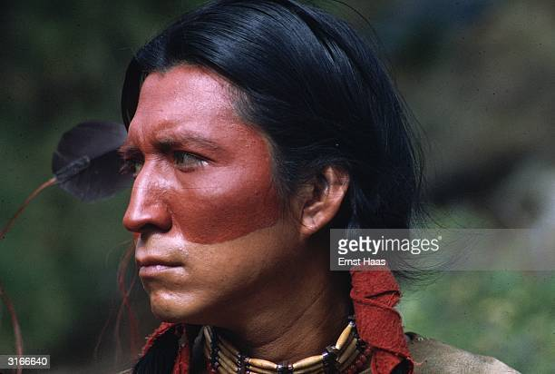 A native American man with painted face long hair and bead necklace