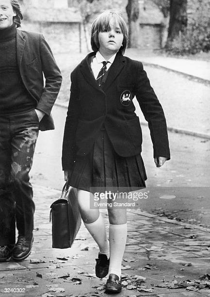 A schoolgirl from Holland Park carrying her satchel