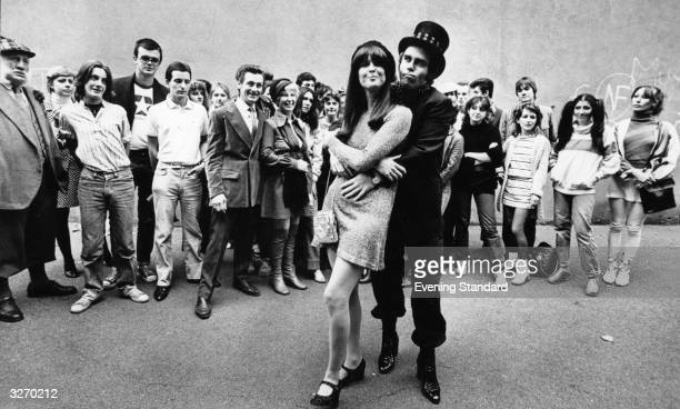 A group of pop fans look on as pop singer and pianist Elton John embraces singer and friend Kiki Dee