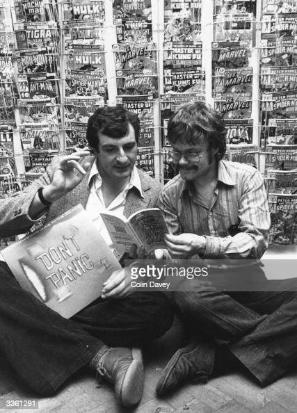 Nick Landau sits on the floor in front of a rack of comics with British author Douglas Adams his book 'The HitchHikers Guide To The Galaxy' and a...