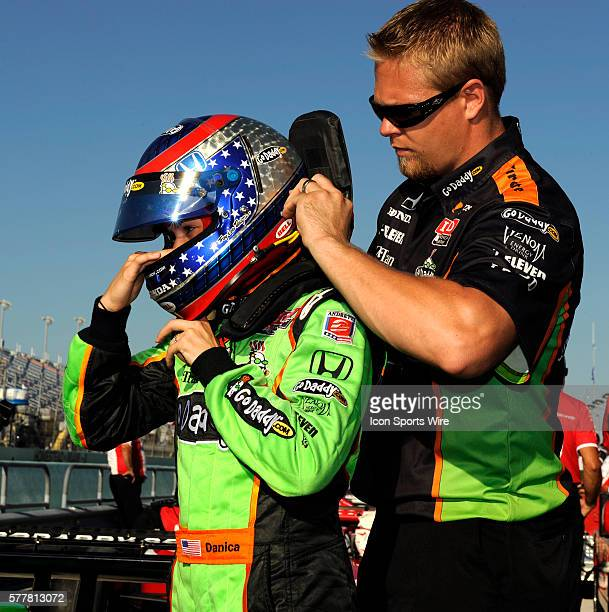 A crew member puts a HANS device on Danica Patrick as she prepares to get in her car on pit row during the qualifying for the Cafes do Brasil Indy...