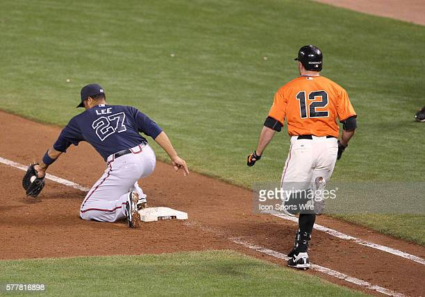 Atlanta Braves first baseman Derrek Lee digs a ball out of the dirt to get San Francisco Giants right fielder Nate Schierholtz out as the Braves Beat...