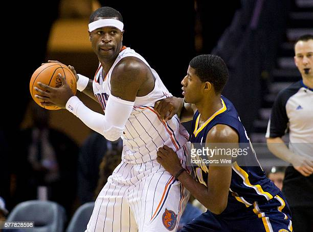 Charlotte Bobcats shooting guard Stephen Jackson looks to pass around Indiana Pacers small forward Paul George during an NBA basketball game at Time...