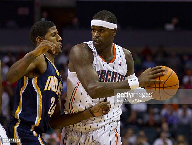 Charlotte Bobcats shooting guard Stephen Jackson works to drive around Indiana Pacers small forward Paul George during an NBA basketball game at Time...
