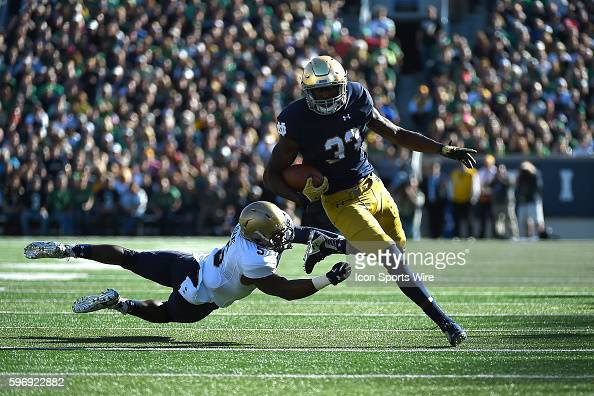 Notre Dame Fighting Irish running back Josh Adams battles with Navy Midshipmen cornerback Quincy Adams in action during a game between the Notre Dame...