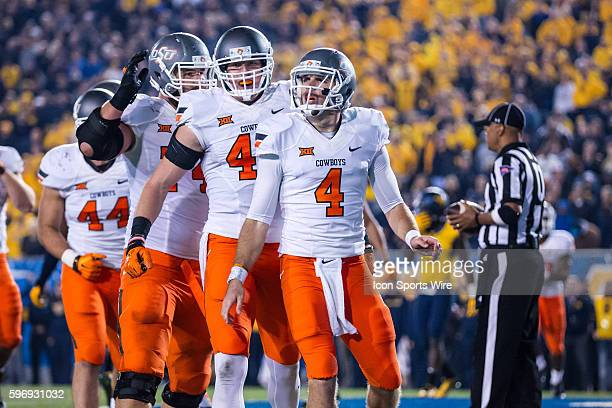 Oklahoma State Cowboys OL Michael Wilson Oklahoma State Cowboys TE Blake Jarwin and Oklahoma State Cowboys QB JW Walsh celebrate after Walsh scored...