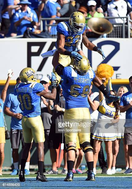 UCLA Conor McDermott lifts UCLA Nate Starks into the air after running for a touchdown during an NCAA football game between the Colorado Buffaloes...