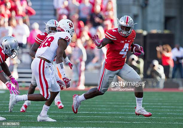 Running back Curtis Samuel of the Ohio State Buckeyes looks to elude the tackle by defensive back A'Shon Riggins of the Indiana Hoosiers during the...