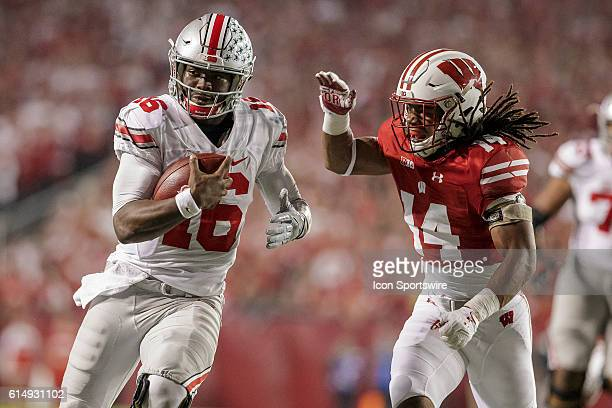 The Ohio State Buckeyes quarterback JT Barrett gets tackled by Wisconsin Badgers safety D'Cota Dixon as the 2nd ranked Ohio State Buckeyes take on...