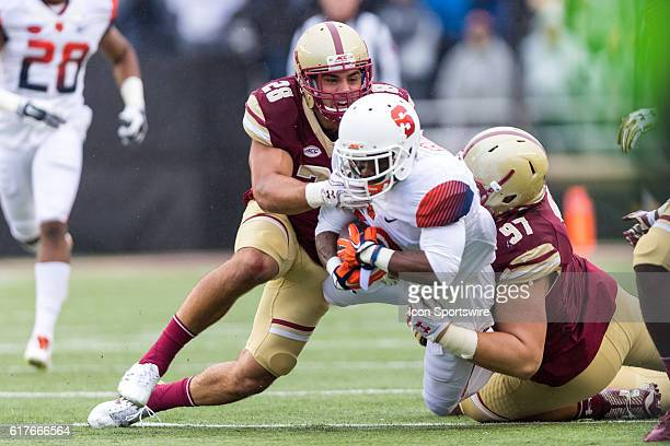 Syracuse Orange wide receiver Brisly Estime is tackled by Boston College Eagles linebacker Matt Milano and defensive tackle Truman Gutapfel during...