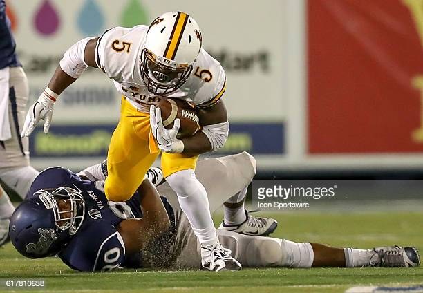 Wyoming Cowboys RB Brian Hill gets tripped up by Nevada DE Malik Reed during the game between the Wyoming Cowboys and the Nevada Wolf Pack played at...