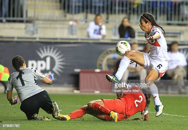 Sydney Leroux of the USA crashes between Dinnia Diaz and Carol Sanchez of Costa Rica during the championship match of the CONCACAF Women's World Cup...