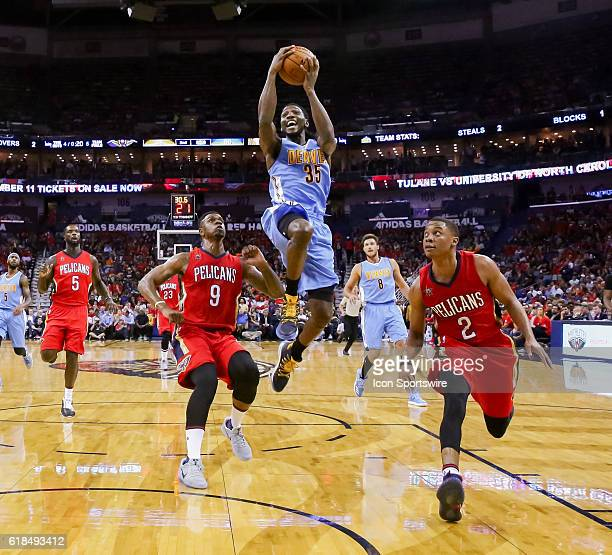 Denver Nuggets forward Kenneth Faried drives to the basket against New Orleans Pelicans guard Tim Frazier and forward Terrence Jones during the game...