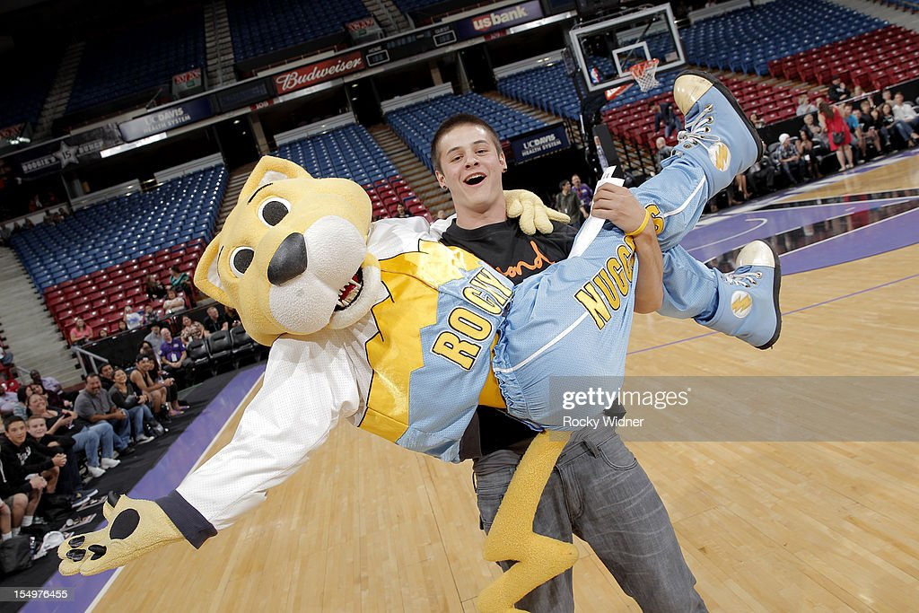A fan of the Sacramento Kings has fun with Rocky mascot of the Denver Nuggets during Open Practice of the Sacramento Kings on October 28, 2012 at Sleep Train Arena in Sacramento, California.
