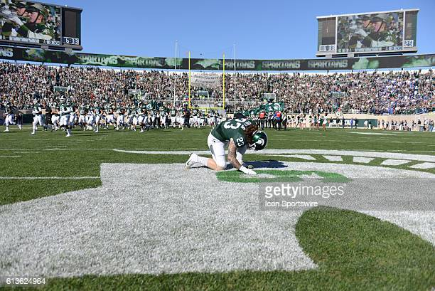 Spartans linebacker Chris Frey honors deceased former Spartans linebacker Mylan Hicks during a nonconference NCAA football game between Michigan...